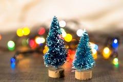 Zwei Weihnachtsbäume auf dem Hintergrund von hellen Geschenken, farbige Lichter, Stockfoto