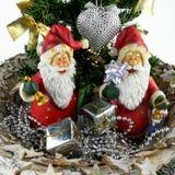 Zwei Weihnachtsmann-Figürchen und Miniweihnachtsbäume lizenzfreie stockfotos
