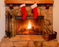 Zwei Weihnachtsstrümpfe auf dem Umhang eines Steinkamins mit einem warmen Feuer stockfoto