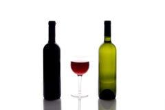 Zwei Weinflaschen und ein Glas Stockfotos