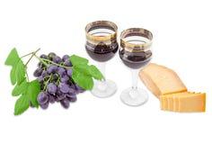 Zwei Weingläser mit Rotwein, Käse und blauer Traube Lizenzfreies Stockbild