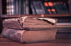 Zwei Weinlese-Bücher, im altem Stil, mit dem unscharfen Bücherregal auf dem Hintergrund stockfoto