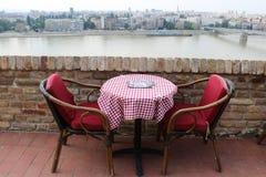 Zwei Weinlesestühle und -Holztisch in einem Café auf dem Flussufer Banken der Donaus, Novi Sad, Serbien lizenzfreie stockfotos