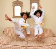 Zwei wenig asiatische Judo gils springen auf Sofa lizenzfreie stockfotografie
