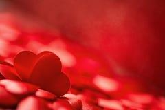 Zwei wenig rote Satinherzen auf rotem Hintergrund, Valentinsgrußtag oder feiern Liebe Stockbild