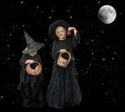 Zwei wenige Halloween-Hexen nachts, mit Sternen und Mond stockbilder