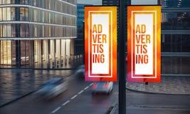 zwei Werbeschilder auf dem Posten nachts Stadt stockfotos