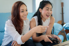 Zwei wettbewerbsfähige Freunde der Frauen, die Videospiele und aufgeregtes ha spielen lizenzfreie stockfotos
