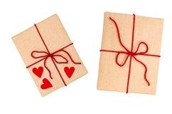 Zwei wickelten braune Geschenkbox mit rotem Band und Herz vom Papier ein, das auf weißem Hintergrund lokalisiert wurde Stockfotografie