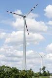Zwei Windenergiemaschinen gegen Wolken Stockfotos