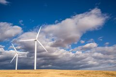 Zwei Windkraftanlagen auf dem goldenen Gebiet vor blauem Himmel und groß Stockfotos