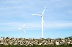 Zwei Windkraftanlagen durch ein altes traditionelles legen am Schweden Steine in den Weg Stockbilder