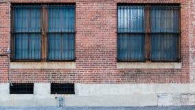 Zwei Windows auf Ziegelsteinrotwand Lizenzfreie Stockfotos