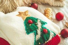 Zwei Winterstrickjacken gelegt auf ein Bett mit Kissen und den Dekorationen des neuen Jahres stockbild