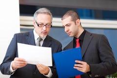 Zwei Wirtschaftler, die im Büro sich besprechen Lizenzfreie Stockbilder