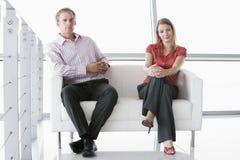 Zwei Wirtschaftler, die im Büro sitzen, beeinflussen das Lächeln stockbilder