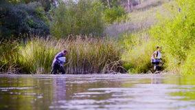 Zwei Wissenschaftlerökologen in den hohen Gummistiefeln gehend in das Wasser des Waldflusses stock footage