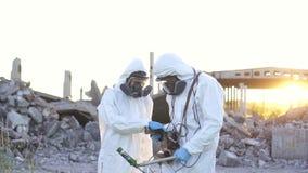 Zwei Wissenschaftler in den Schutzanzügen und in den Masken und ein persönlicher ionisierender Strahlendosimeter, gehen Maßstrahl stock footage