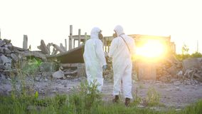 Zwei Wissenschaftler in den Schutzanzügen und in den Masken und eine Strahlungsaufsichtskraft, gehen Maßstrahlung auf dem Hinterg stock footage
