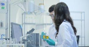 Zwei Wissenschaftler der medizinischen Forschung arbeitet mit Beispielisoliert Kasten stock footage
