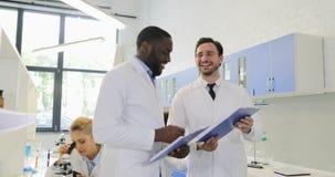 Zwei Wissenschaftler, die Dokumente mit Experiment verwahren, resultiert sprechendes glückliches lächelndes und rüttelndes Handzu stock video