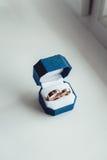 Zwei wite Eheringe im blauen Kasten auf einem weißen Fensterbrett Lizenzfreies Stockbild