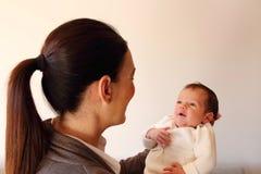 Zwei-Wochen-alter lächelnder kleiner Babygriff durch seine Mutter ` s Hände Stockbild