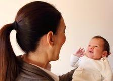 Zwei-Wochen-alter lächelnder kleiner Babygriff durch seine Mutter ` s Hände Stockfotos