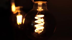 Zwei Wolframglühlampelampen über schwarzem Hintergrund Konzept von hellem und von Dunklem, Idee, Strom am modernen Haus stock video