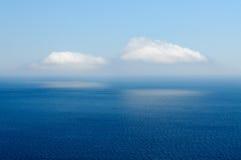 Zwei Wolken reflektiert im Meer Stockfoto