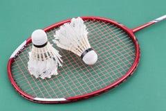 Zwei worned heraus Badmintonfederball mit Schläger auf grünem Gericht Stockbild
