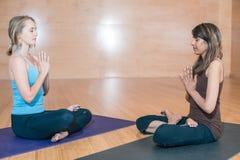 Zwei yound Frau: ein blondes kaukasisches und indisches Sitzen in einem Lotussitz in einem Yogastudio Lizenzfreies Stockfoto