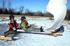 Zwei Young Boys auf Eis-Boot mit Segeln stockbild
