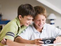Zwei Young Boys, das mit einem HandVideospiel spielt Lizenzfreies Stockbild