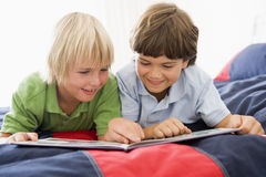 Zwei Young Boys, das sich auf einem Bett liest ein Buch hinlegt Stockbilder
