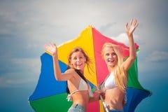 Zwei ypung Frau aqnd coloful Regenschirm, der Spaß auf dem Strand hat stockfoto