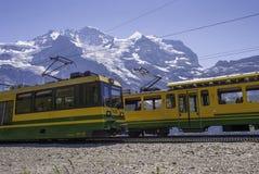 Zwei Züge sind auf Eisenbahnlinien in den Bergen von der Schweiz stockfotografie