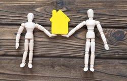 Zwei Zahlen eines Mannes von einem Baum halten ein Haus in ihren Händen Lizenzfreie Stockfotos