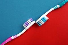 Zwei Zahnpasten auf einem roten und blauen Hintergrund stockfotos