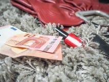 Zwei zehn Euroanmerkungen, die nahe bei einer roten Handtasche liegen Stockbild
