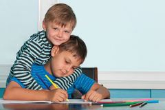 Zwei zeichnende Jungen am Schreibtisch Stockbilder