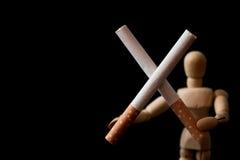 Zwei Zigaretten in der Querform, die durch hölzernen Mann hält, stellen dar, das verlassene `, Sie können es tun ` Konzept Lizenzfreie Stockfotos