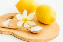 Zwei Zitronen, ein hölzerner Löffel mit Salz und eine Blume der Narzisse auf einem hölzernen Brett stockbild