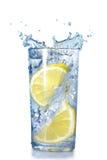 Zwei Zitronen fielen in ein Glas Lizenzfreies Stockfoto