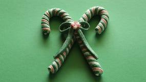 Zwei Zuckerstangen gebunden zusammen mit einem Bogen auf einem grünen festlichen Hintergrund stockbilder