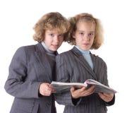 Zwei Zwillinge mit Lehrbuch Lizenzfreies Stockbild