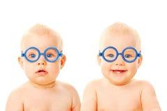 Zwei Zwillingsschätzchenjungen, die Gläser tragen. Lizenzfreies Stockbild