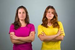Zwei Zwillingsschwestern mit den gekreuzten Armen stockfotos