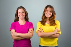 Zwei Zwillingsschwestern mit den gekreuzten Armen lizenzfreies stockbild