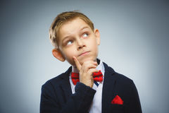 Zweifel, Ausdruck und Leutekonzept - Junge, der über grauem Hintergrund denkt Lizenzfreies Stockbild